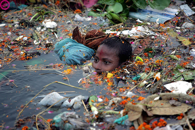 Boy swimming in polluted water in India