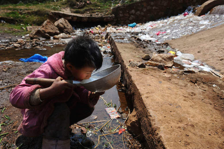 Child drinks water from stream in Fuyuan County, China