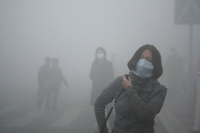Girl walks through smog in Beijing, where small-particle pollution is 40 times higher than acceptable levels established by the WHO