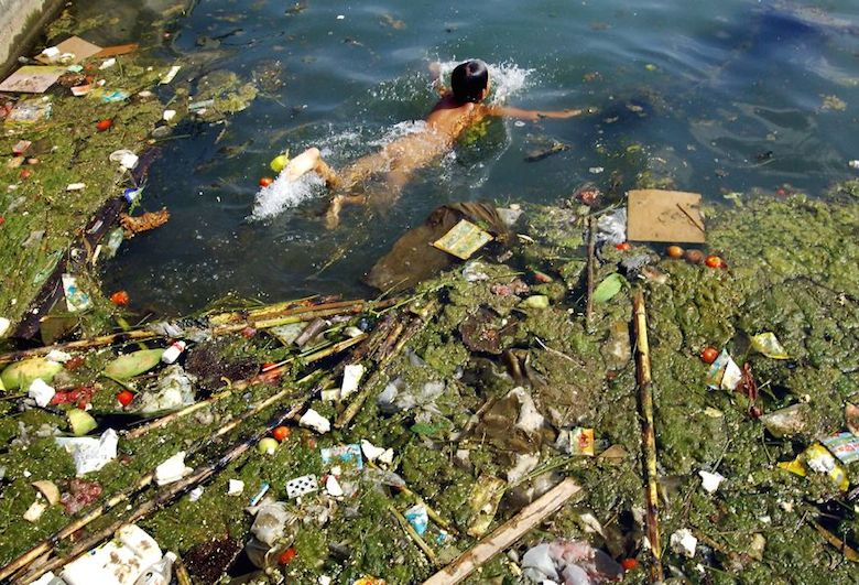 A child swims in a polluted reservoir in Pingba, China
