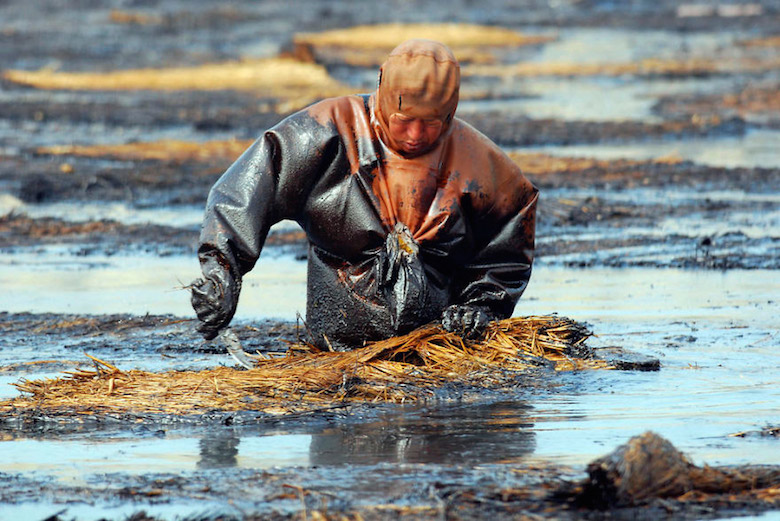 Man cleans up oil spill in Dalian Port, China