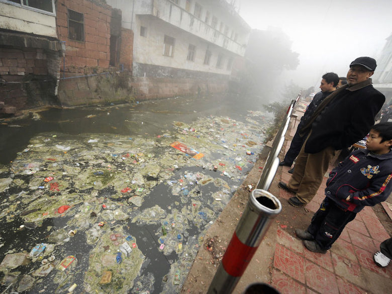 Residents look at a heavily polluted river in Zhugao, China