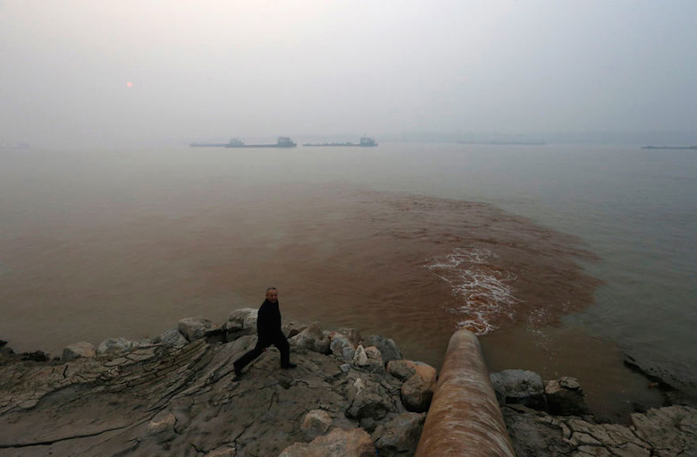 A man walks by a pipe discharging waste water into the Yangtze River, China